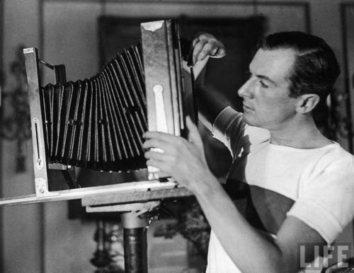 Photographer Cecil Beaton adjusting the lens on a primitive camera in his studio-- Circa 1929.