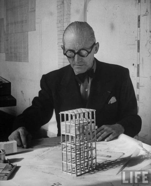 Architect Le Corbusier studying architectural plans & small model of building in his office-- Paris, France 1946.