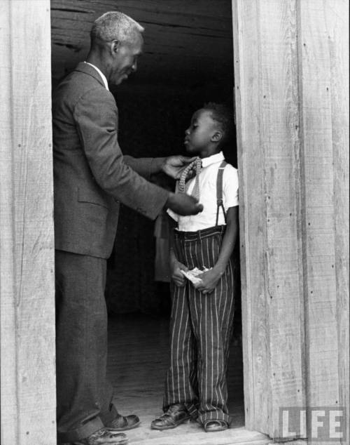 Plantation sharecropper Lonnie Fair helping his son dress in preparation for Sunday church services-- MS, 1936.