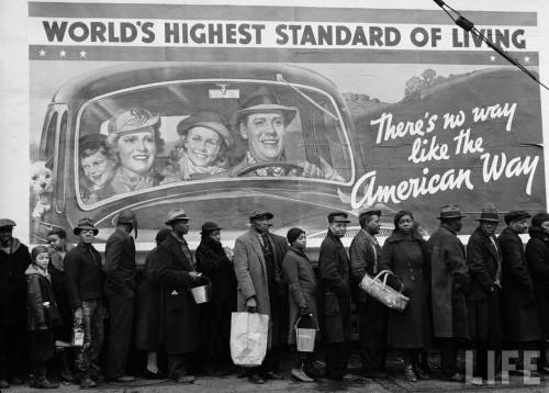 Famous image of African American flood victims lined up to get food & clothing fr. Red Cross relief station in front of billboard ironically extolling WORLD'S HIGHEST STANDARD OF LIVING/ THERE'S NO WAY LIKE THE AMERICAN WAY-- Louisville, KY 1937.