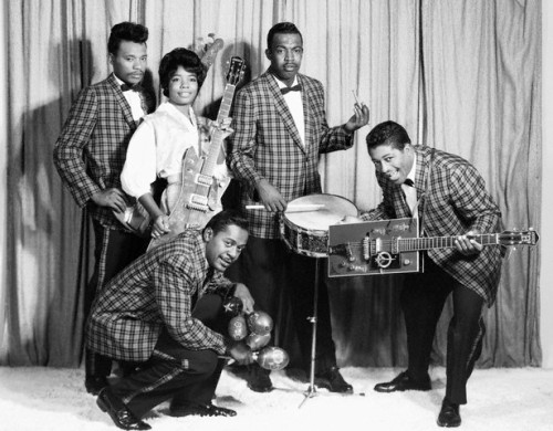 "Norma-Jean ""The Duchess"" Wofford in white blouse, Jerome Green squatting in front with maraca, and Bo Diddley with his signature Gretsch guitar --late 1950s."
