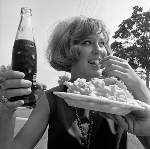 FOOD'S FUN-- Nancy Kennedy, 20, downs diet cola and french fries, popular combination with the young set. The theory is that diet drink saves enough calories to allow for the fattening french fries.  L.A. Times --1965.