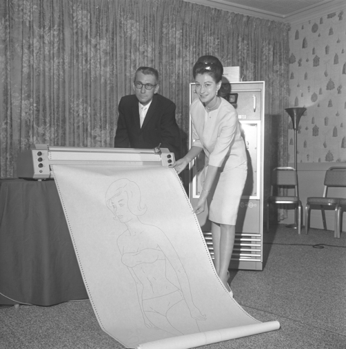 "PERFECTION?-James L. Pyle and Nonna Walls examine ""Miss Formula"", a computer-created drawing resulting from a list of ""perfect female"" statistics, CA 1964."