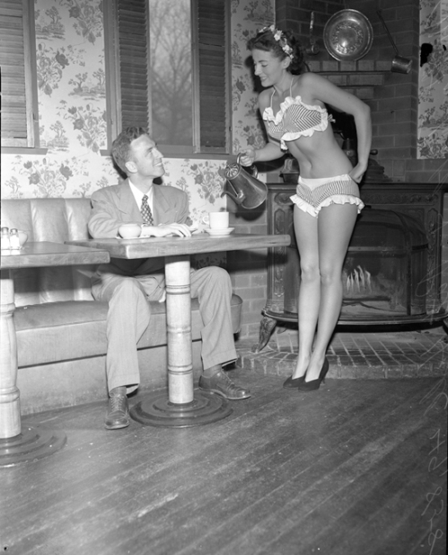 "Pat Hall, ""Miss 7-Cent Cup of Coffee, 1950,"" serving William E. Kinman coffee while wearing a bikini, Los Angeles, CA  --1950."