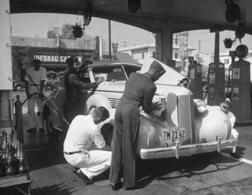 Muller Brothers Service Station's white uniformed attendents pumping gas & inflating tires on a fancy convertible while their uniformed African-Amer. conterparts wield rags as they polish the windshield & chrome --ca. 1938.