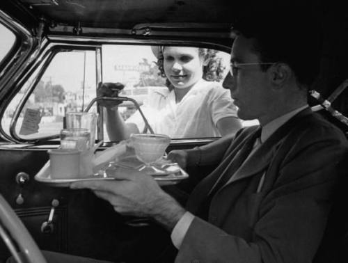 Carhop taking tray of dirty dishes off car window for passenger in car at drive-in soda fountain --ca. 1938.